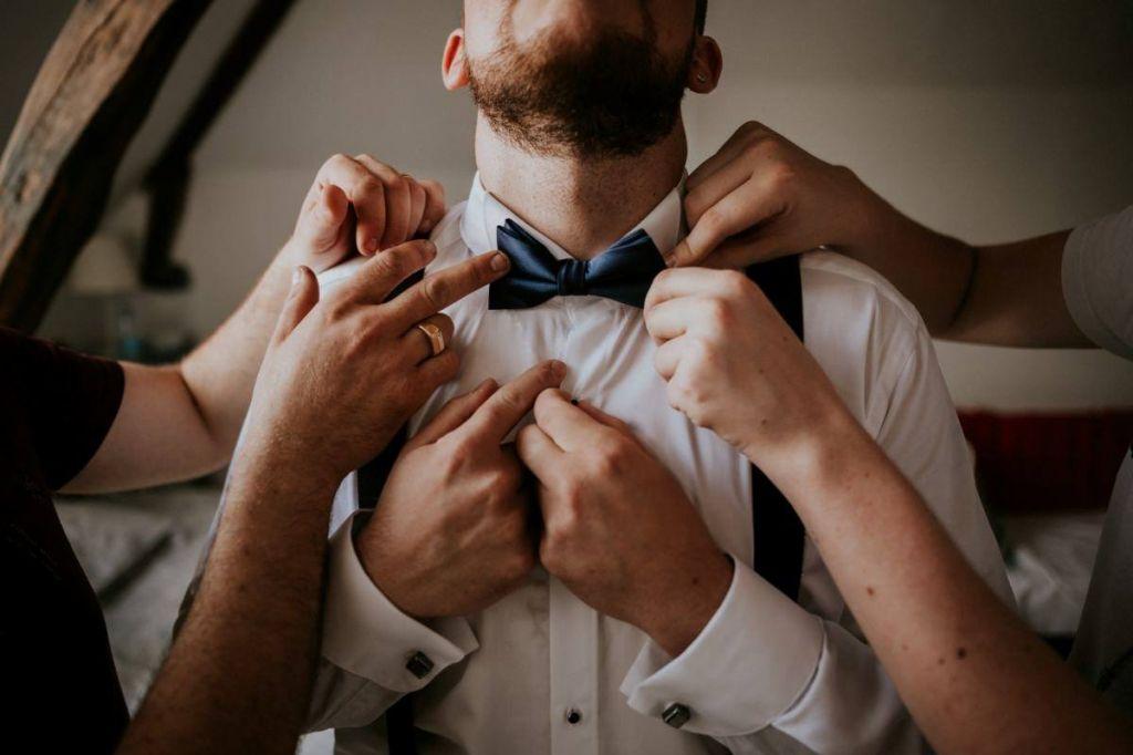 le futur marié le matin du mariage, habillage de monsieur (chemise, noeud papillon) aidé par les garçons d'honneur