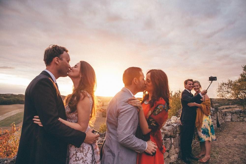 Le couple de mariés prend une photo au smartphone avec une perche à selfie. Les témoins s'embrassent au même moment pour une photo de groupe originale.
