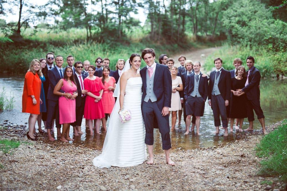 Une photo de groupe les pieds dans l'eau où les mariés et leur invités profitent de la rivière pour se rafraichir !