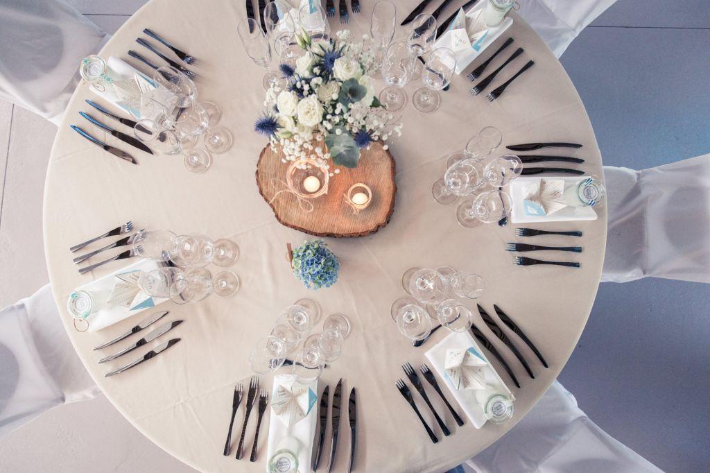 Couverts argentés, verres en cristal élégants et rondin de bois agrémenté d'un bouquet de fleurs en centre de table, on adore cette décoration simple et raffinée ! Photo ©Didier Kapitza. Trouvez le photographe de mariage qui correspond à votre style sur www.regardauteur.com #mariage #wedding #photographe #table #décoration #couverts #rondin #bois #centredetable #bouquet #fleurs #cristal  #houssechaise #nappe