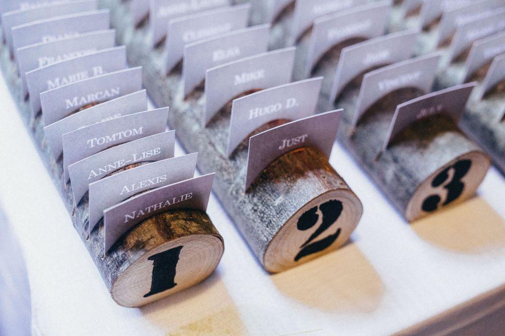 Etiquettes de table - Voici une idée originale pour la répartition des invités !  Photo ©Juliette Devynck. Trouvez le photographe de mariage qui correspond à votre style sur www.regardauteur.com #mariage #wedding #photographe #décoration #rondins #plandetable #étiquettes #papeterie