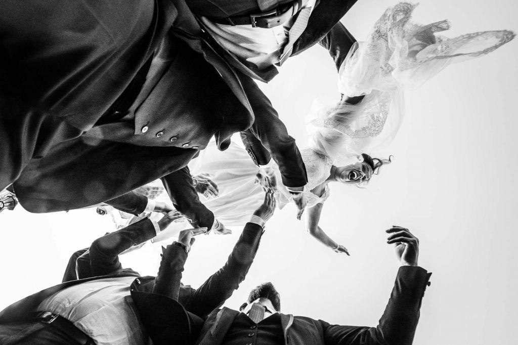 La mariée dans les airs - Lorsque ce sont les hommes qui portent la mariée ! Photo ©Benjamin Brette. Trouvez le photographe de mariage qui correspond à votre style sur www.regardauteur.com #mariage #wedding #photographe #photo #groupe #mariée #noiretblanc #garçonsdhonneur