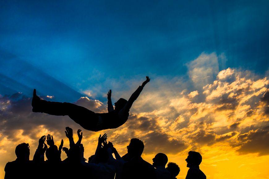 Le marié et ses garçons d'honneur - Le marié jeté en l'air dans le ciel coloré ! Photo ©Alison Bounce. Trouvez le photographe de mariage qui correspond à votre style sur www.regardauteur.com #mariage #wedding #photographe #groupe #marié #garçondhonneur #ciel #lumière