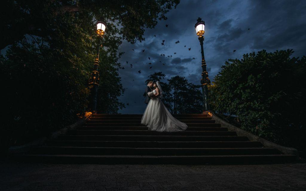 Photo de couple en extérieur -  Escaliers somptueux, lampadaires anciens et feuilles qui s'envolent à la tombée de la nuit … Photo ©Olivier Fréchard. Trouvez le photographe de mariage qui correspond à votre style sur www.regardauteur.com #mariage #wedding #photographe #couple #nuit #escalier #lampadaires #film #robe #mariée