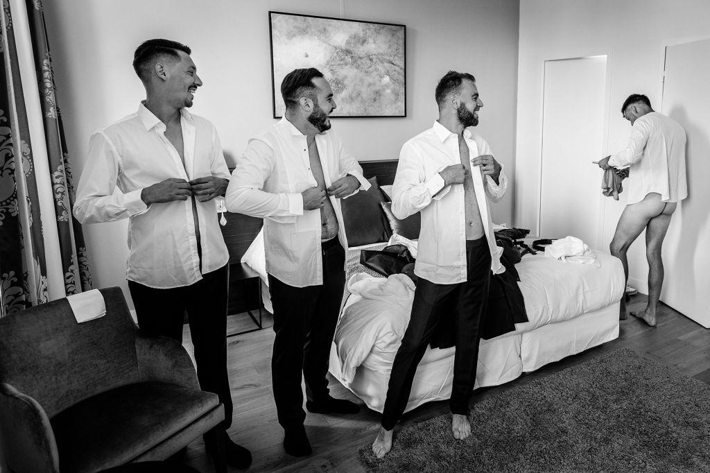 Les costumes - Voici une photo pleine d'humour du marié et de ses garçons d'honneur qui s'habillent ! Photo ©Florent Cattelain. Trouvez le photographe de mariage qui correspond à votre style sur www.regardauteur.com #mariage #wedding #photographe #préparation #marié #garçonsdhonneur #noiretblanc #humour #costumes