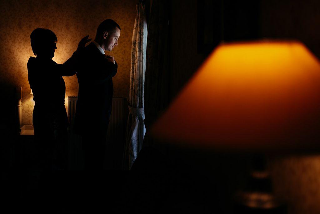 Le costume - Comme une ombre dans l'obscurité qui aide le marié à se préparer… Photo ©Olivier Fréchard. Trouvez le photographe de mariage qui correspond à votre style sur www.regardauteur.com #mariage #wedding #photographe #préparation #marié #ombre #costume
