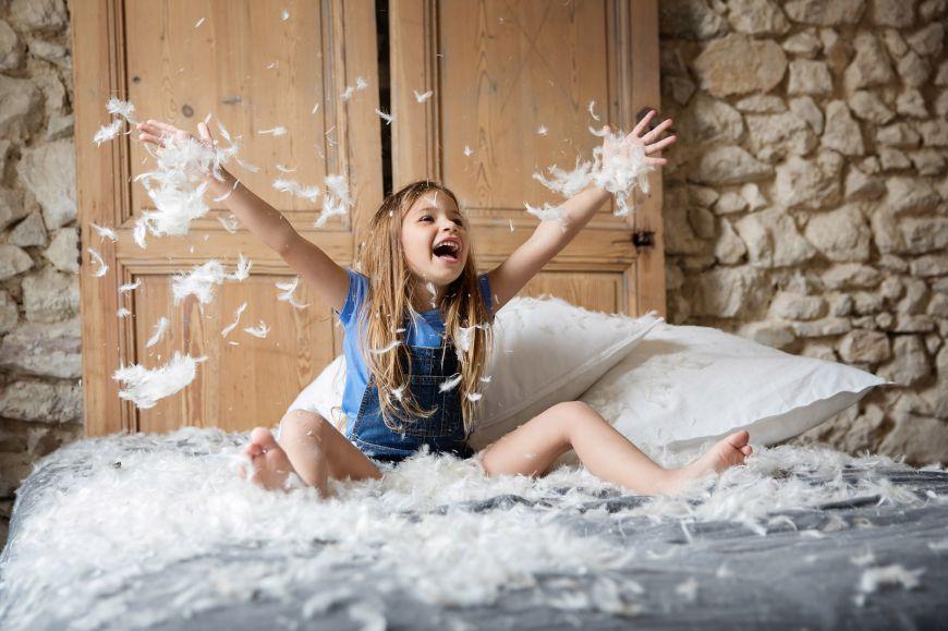 Un portrait amusant de cette jeune fille dans des plumes de polochons ! Photo @Lisa Tichané  Trouver votre photographe portrait sur www.regardauteur.com/fr  #enfant #fille #plumes #fun #jeu #rire #portrait #photographe #photographie #photography #regardauteur