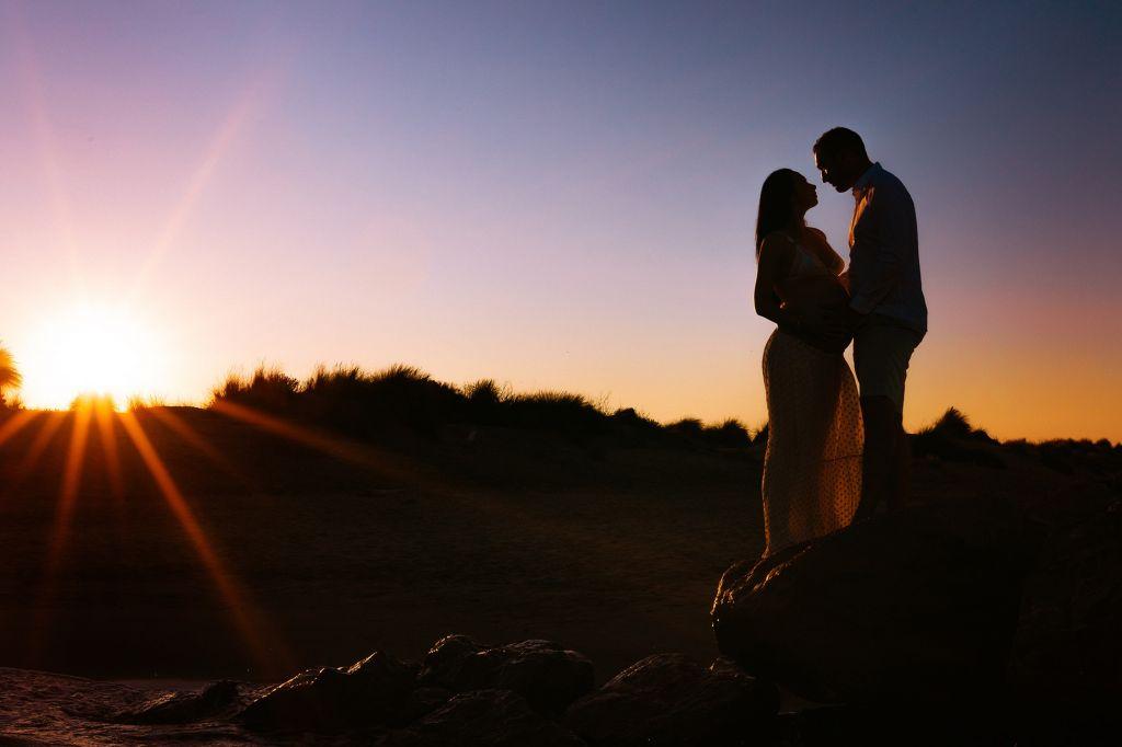 photo grossesse couple champ large et coucher de soleil